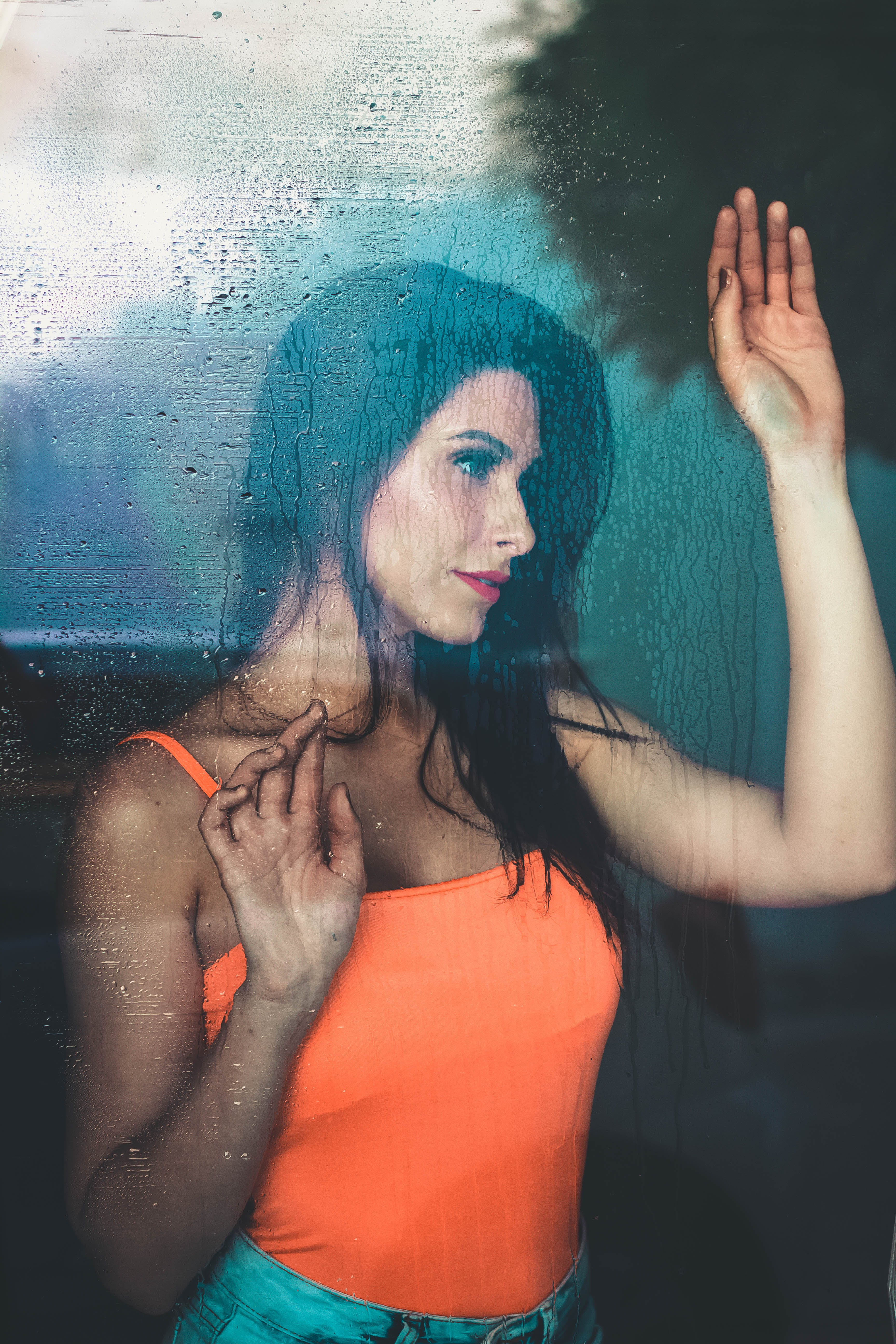 Photo of Woman Leaning Against Window Looking Outside