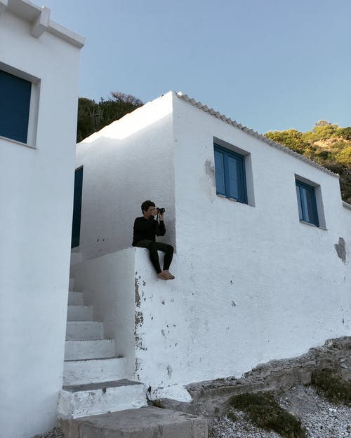 Man Sitting Near White Building