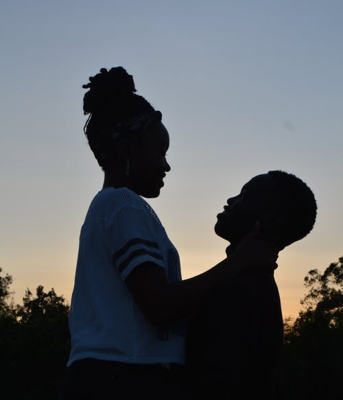 Side view of young African American couple hugging each other and enjoying time together against cloudless sundown sky in evening