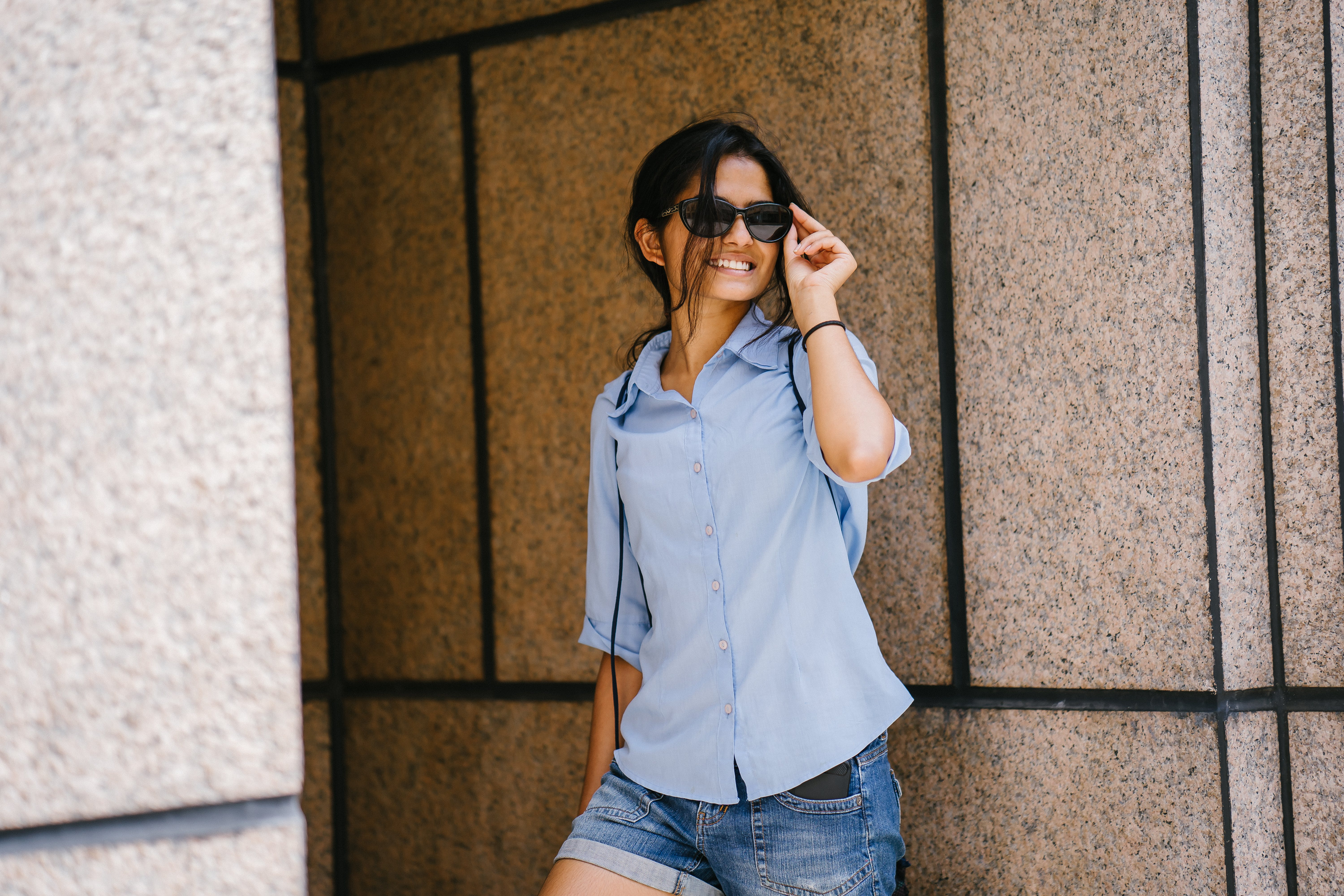 Photo of Smiling Woman in Blue Dress Shirt and Denim Shorts