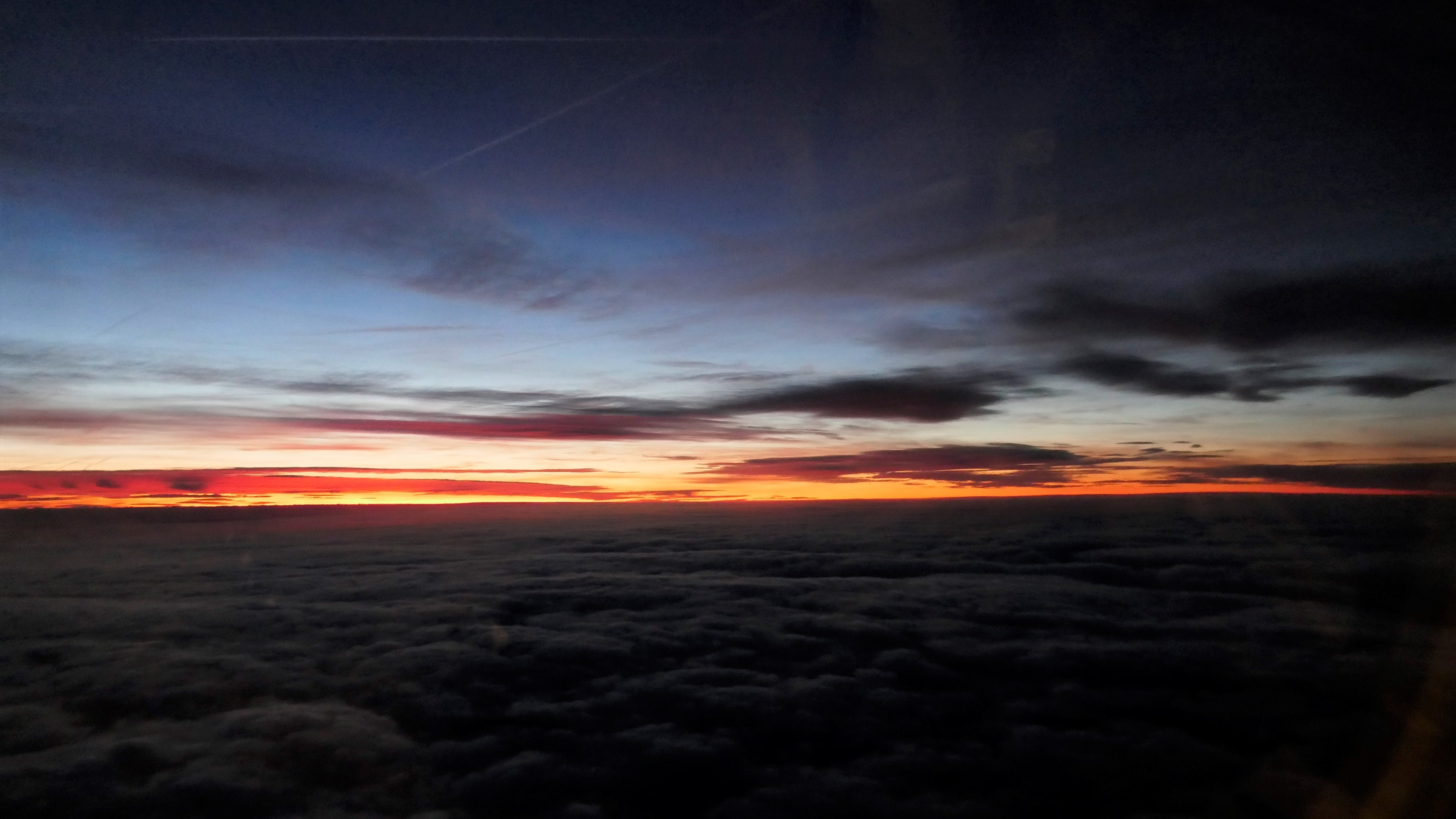 Free stock photo of airplane view, gold light to darkness, Sunset over the clouds