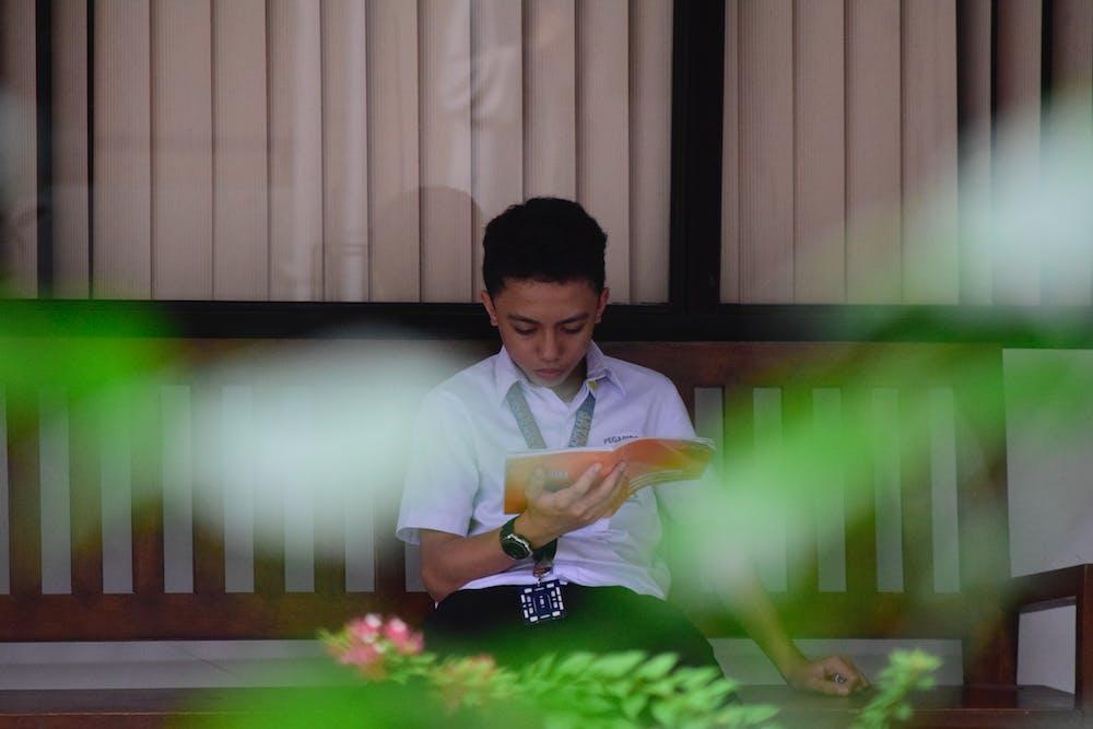 Boy reading a book. | Photo: Pexels