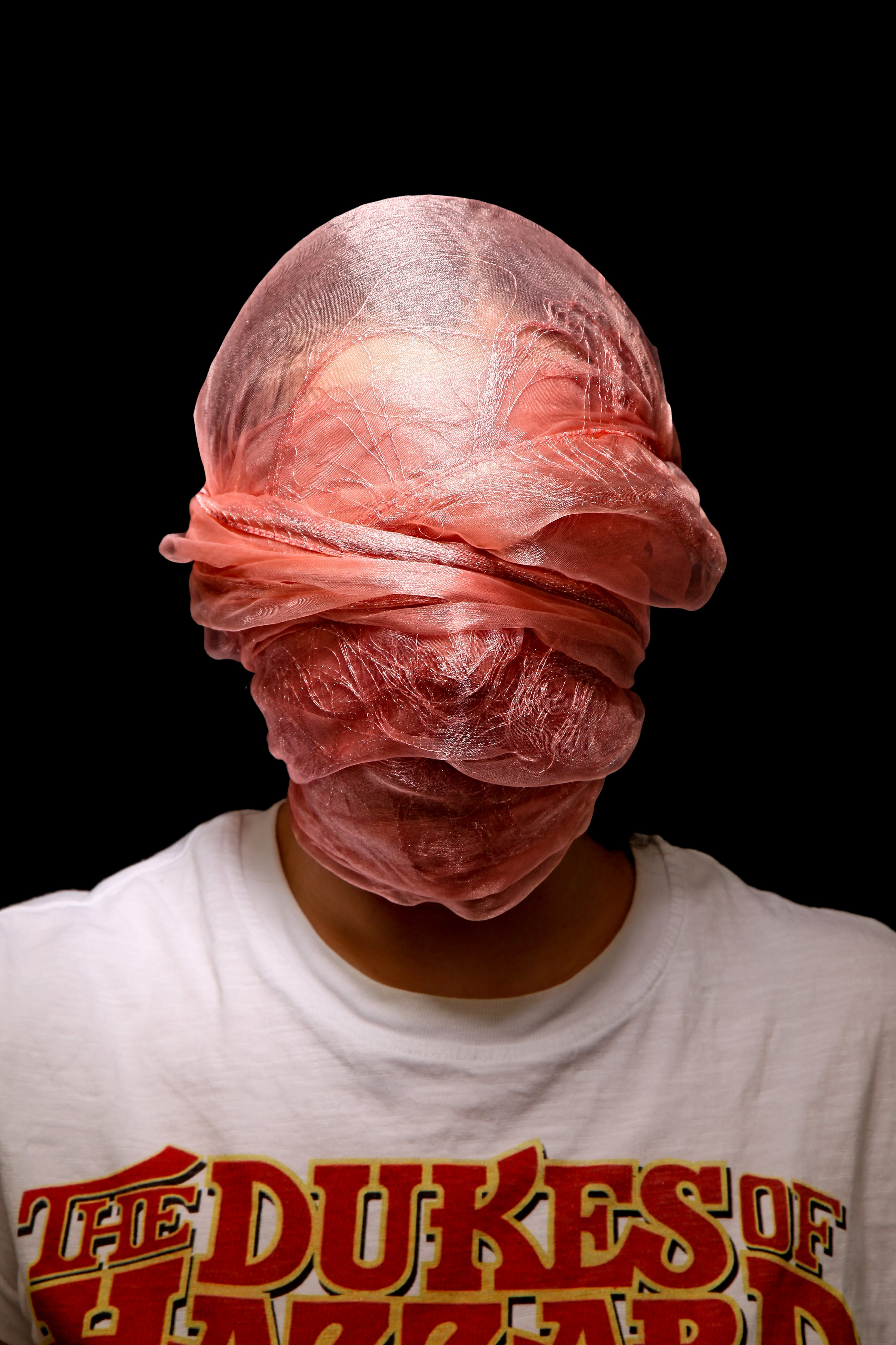 Person in t shirt covering their face with a scarf