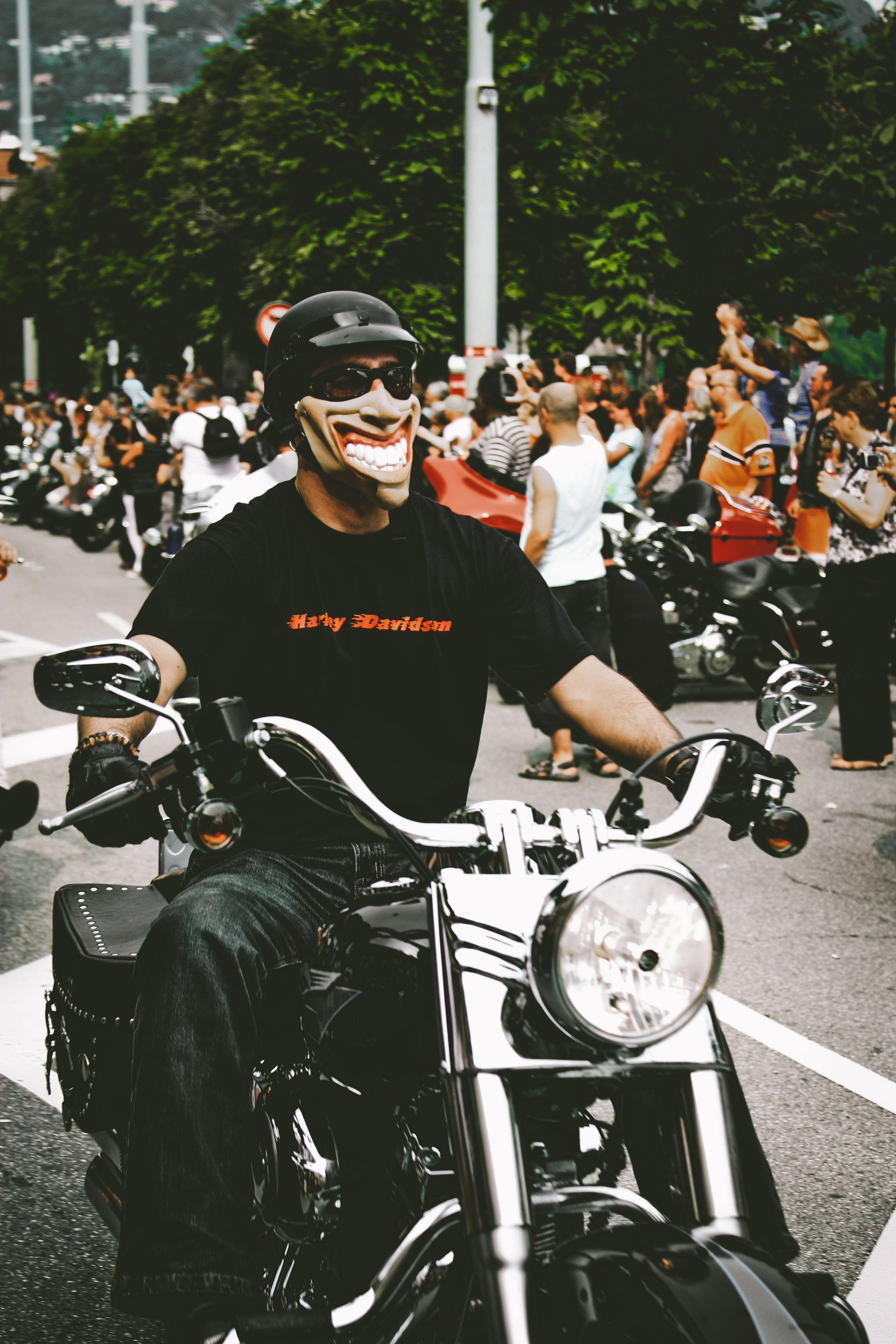 Photo of Man Riding Motorcycle While Wearing Mask