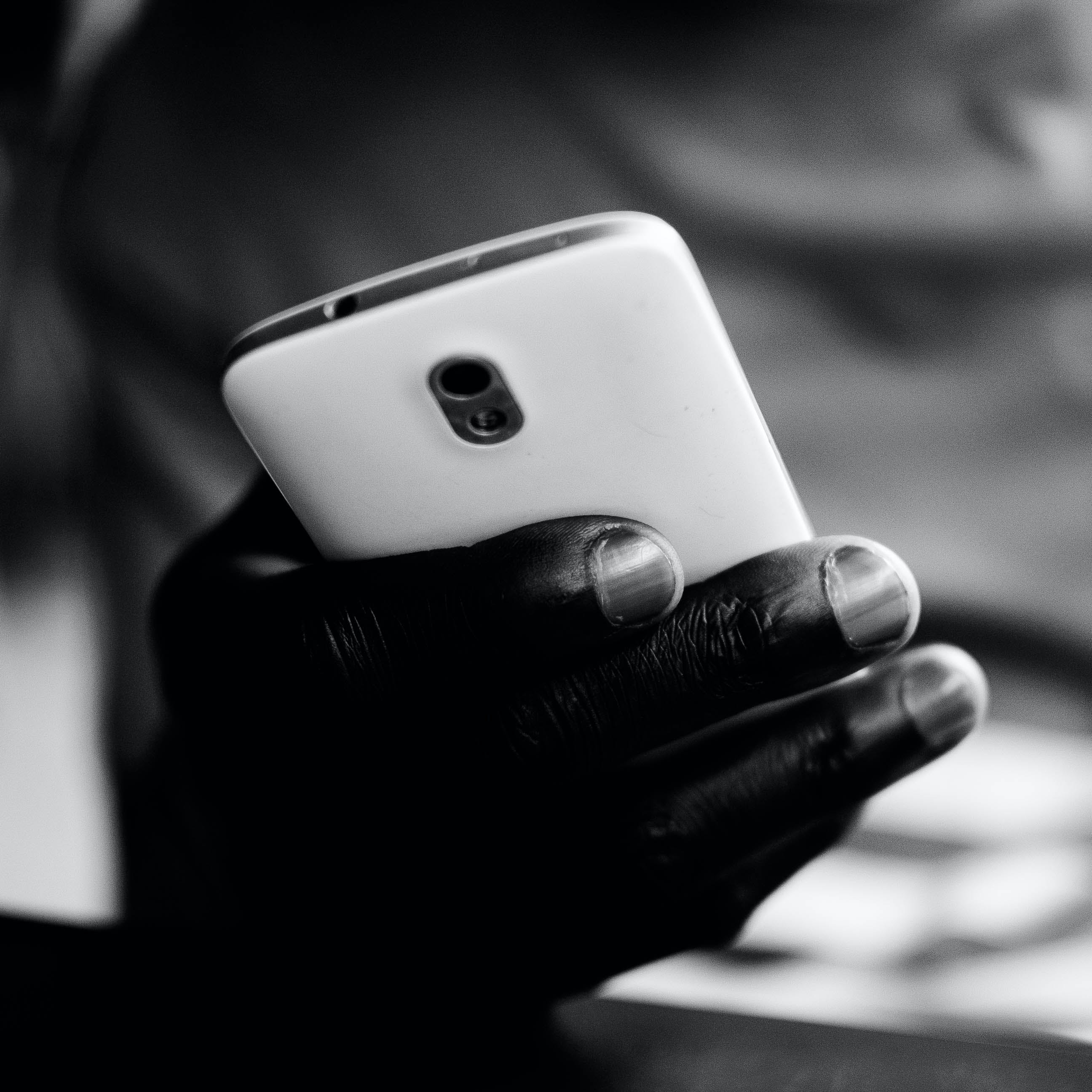 Black and White Photo of Person Holding a Mobile Phone