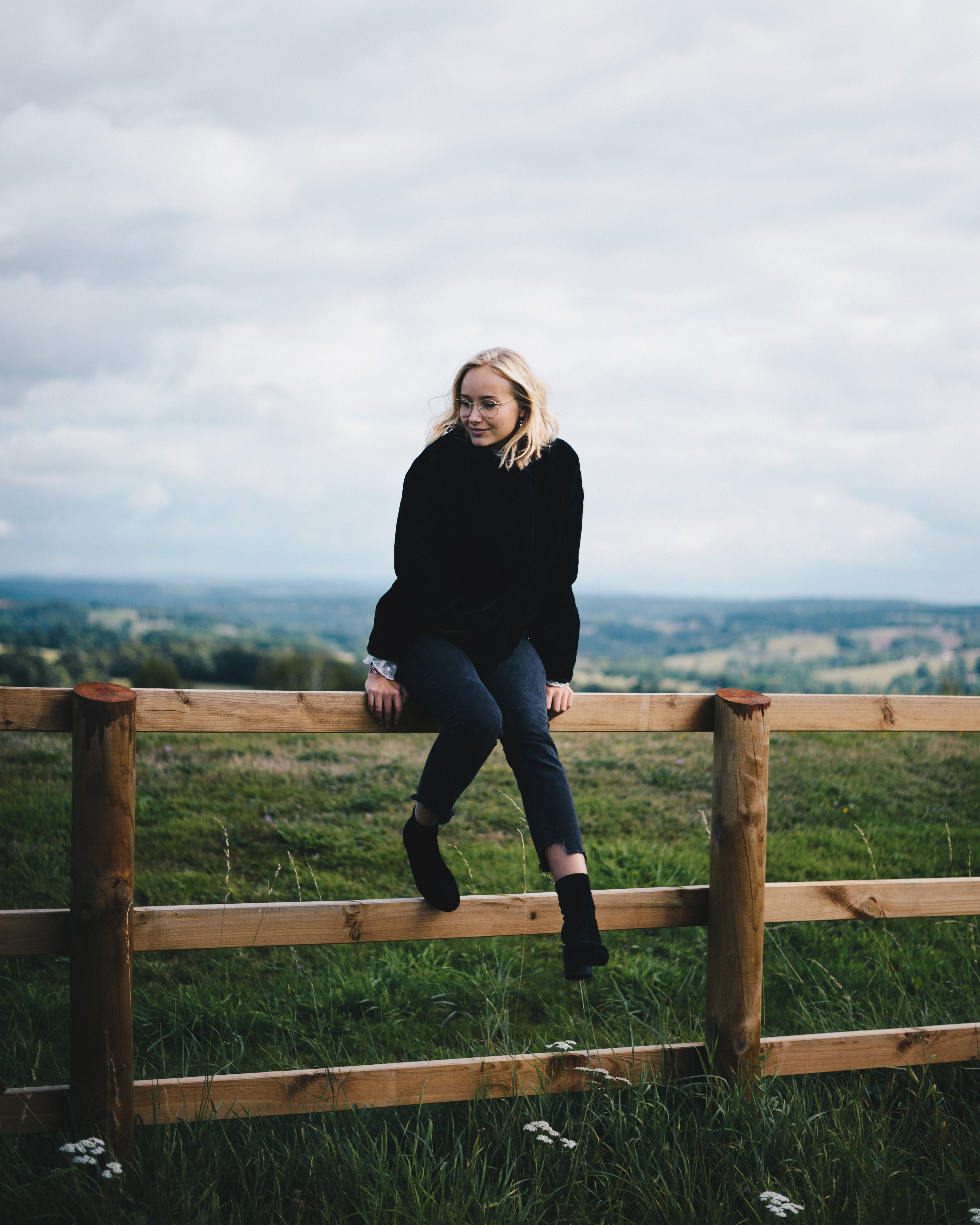 Photo of Woman Sitting on Wooden Fence