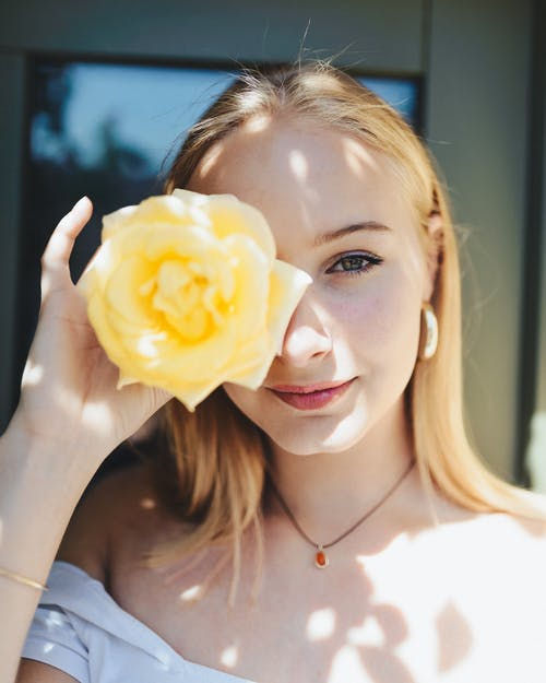 Close-Up Photo of Woman Holding Flower