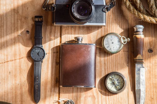 Brown Wine Flask Near Lomo Camera Watch Knife and Pocket Watches on Able