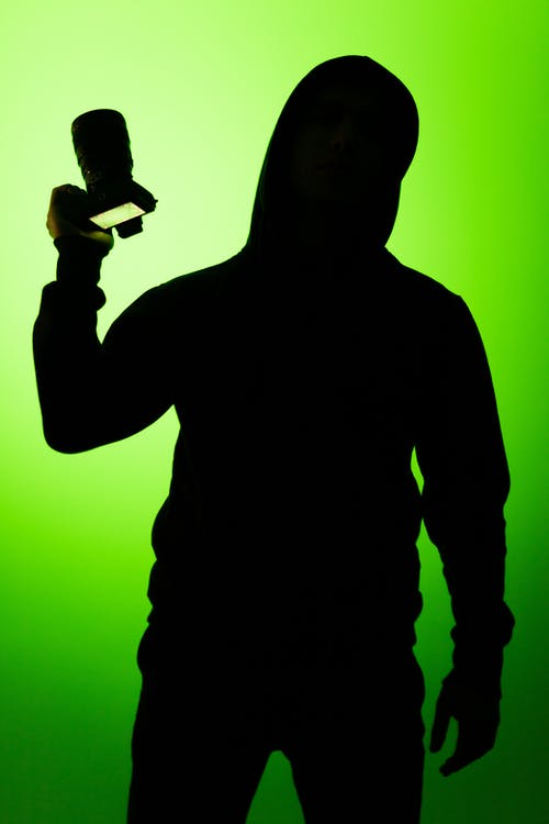 Silhouette Of Person Holding A Camera