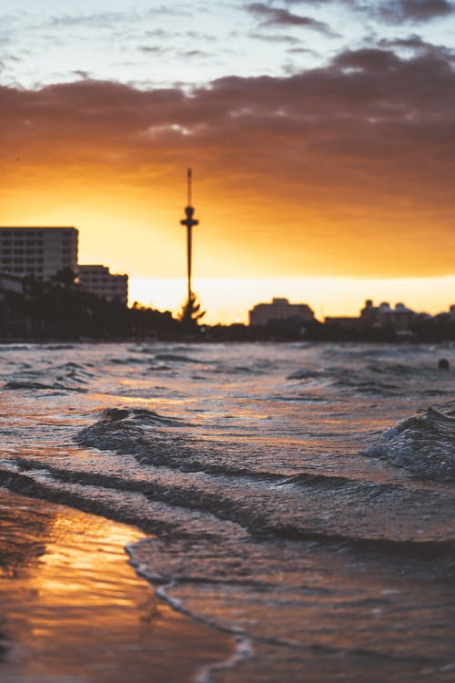 Photos gratuites de aube, bâtiments, bord de mer, ciel
