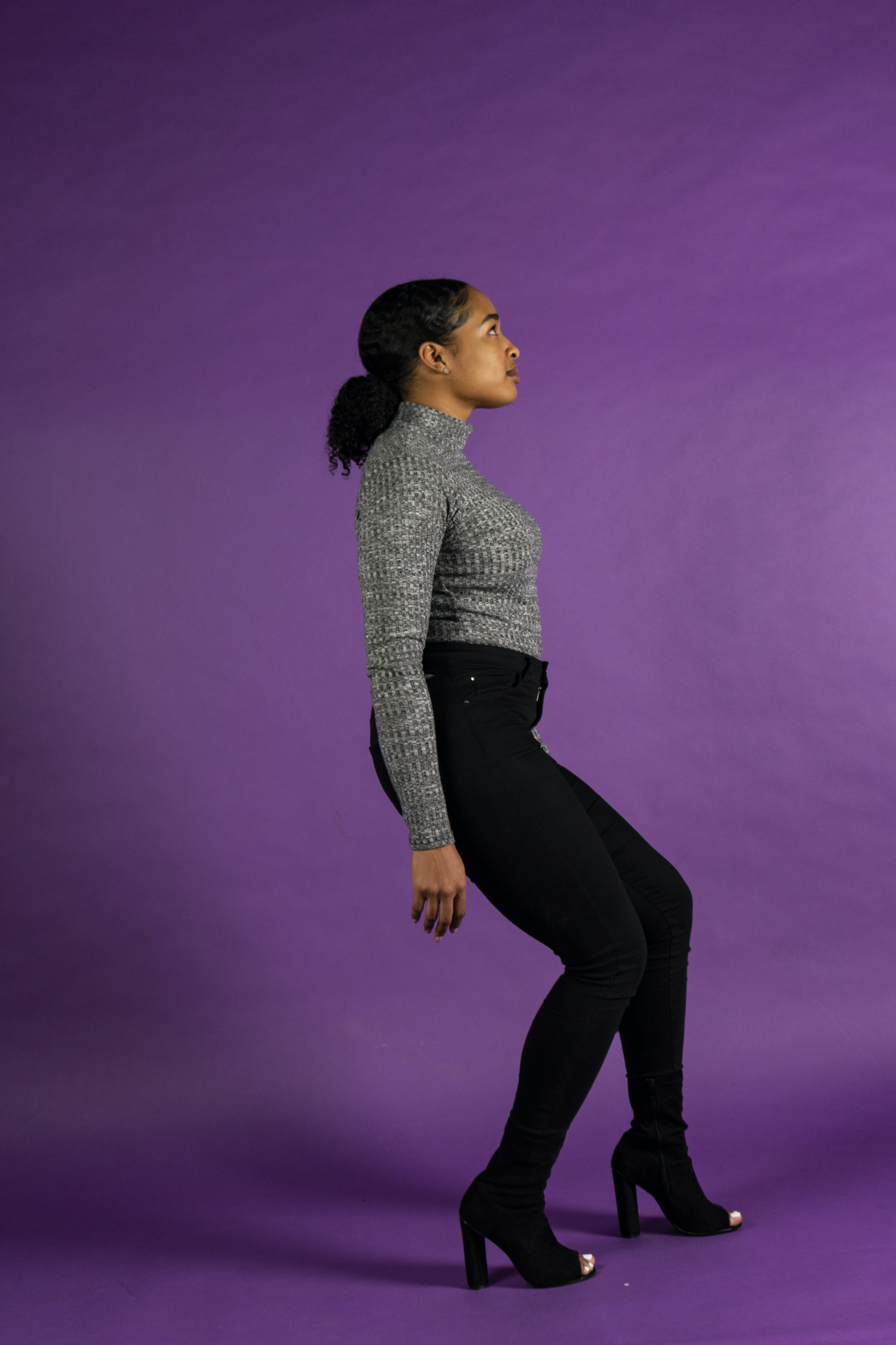Woman in Grey Turtleneck and black Pants Posing