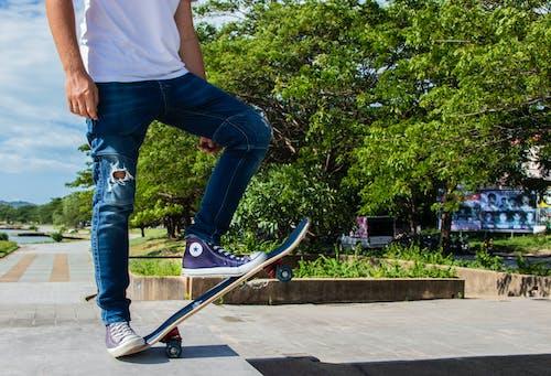 Foto profissional grátis de ação, all star, andar de esqueite, andar de skate