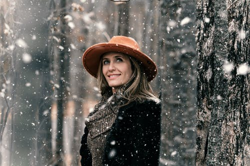 Smiling Woman Standing Near Tree With Snow Falling