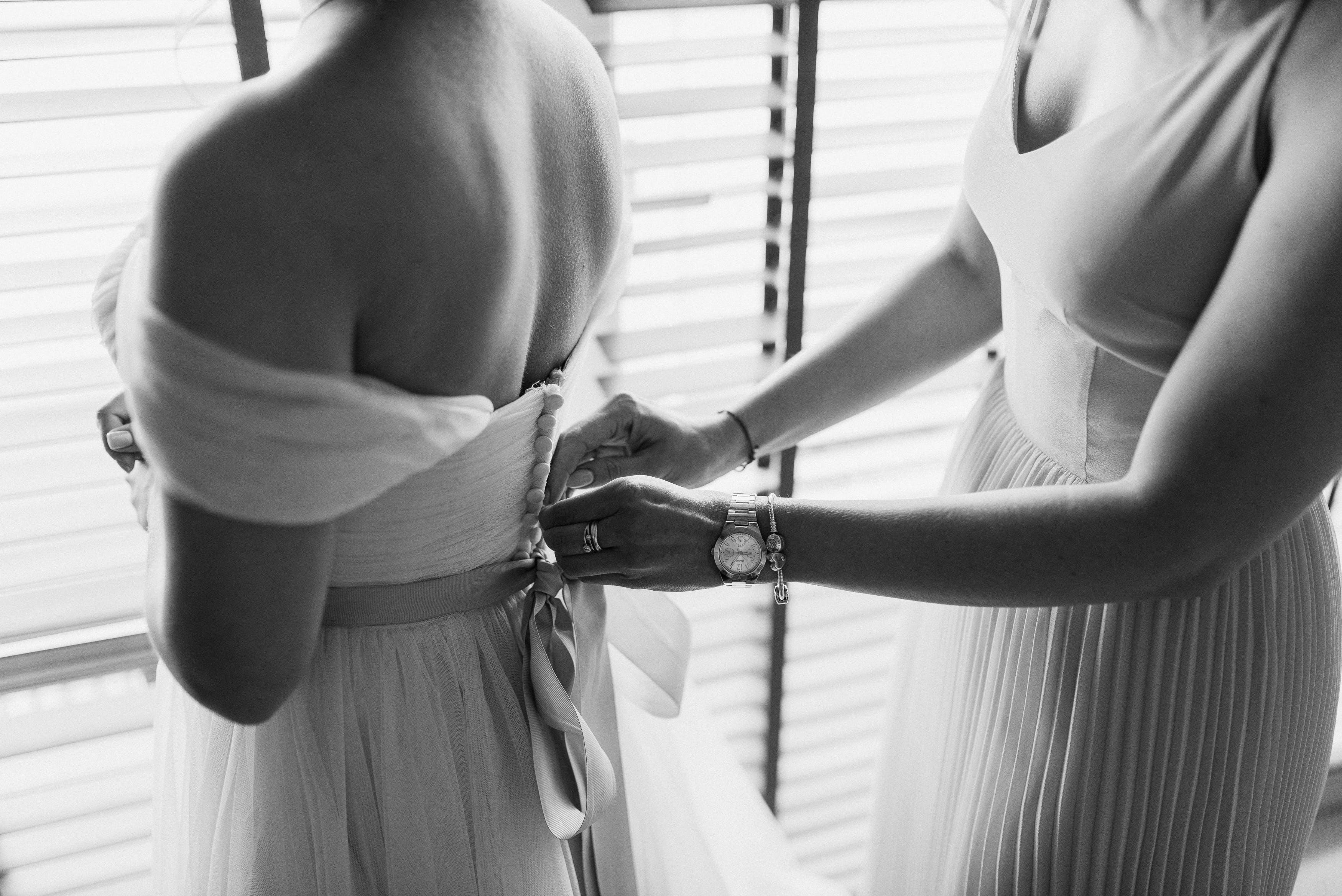 Woman Fixing Dress Of Woman