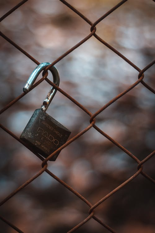Close-Up Photo Of Padlock Hanging On Chain-link Fence