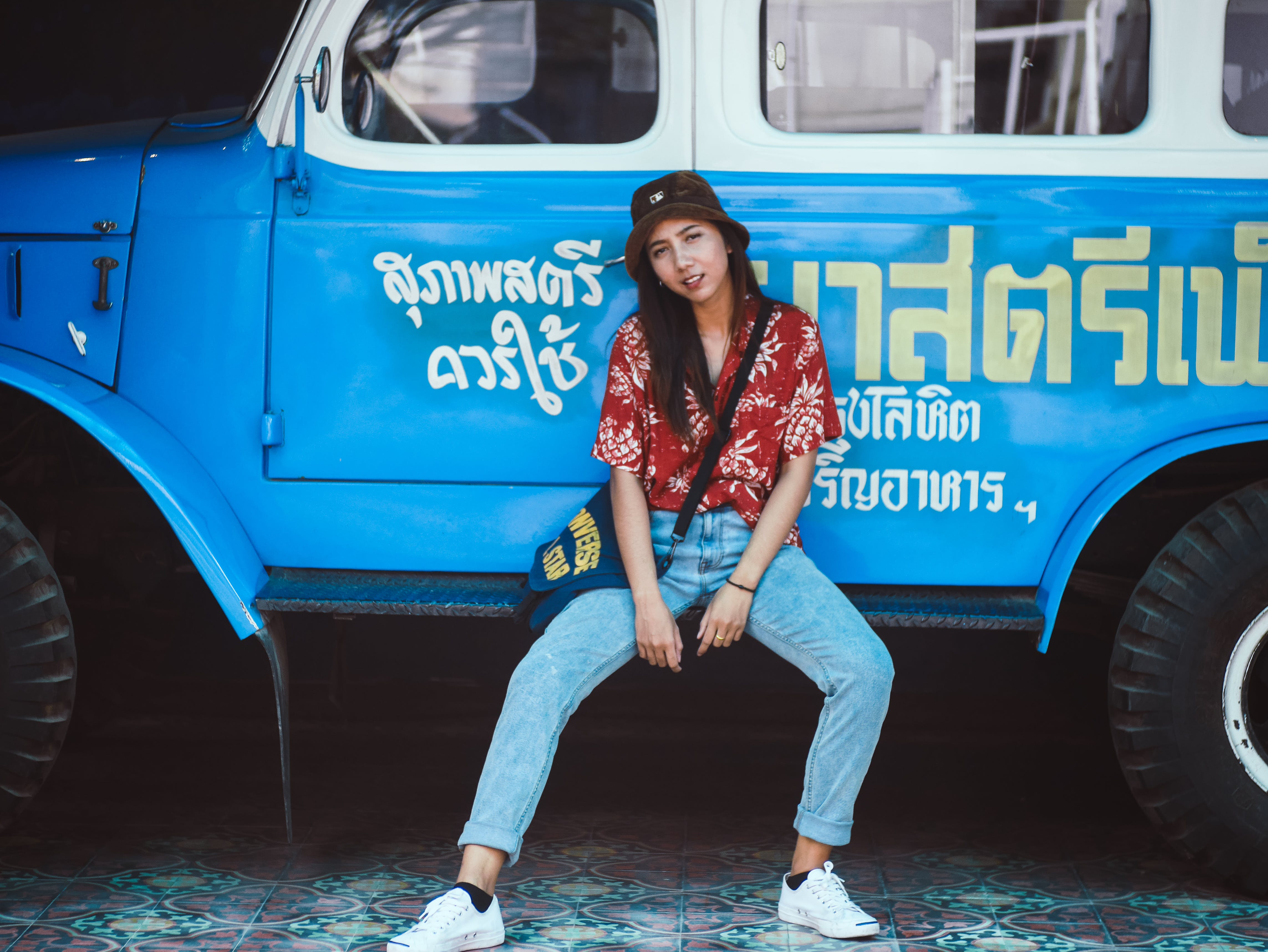 Photo of Woman Sitting on Blue Truck's Side Step