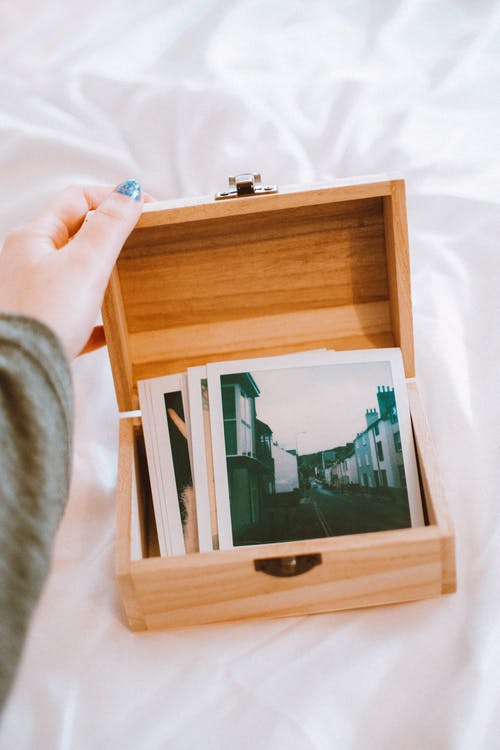 Close-Up Photo of Pictures On Wooden Box