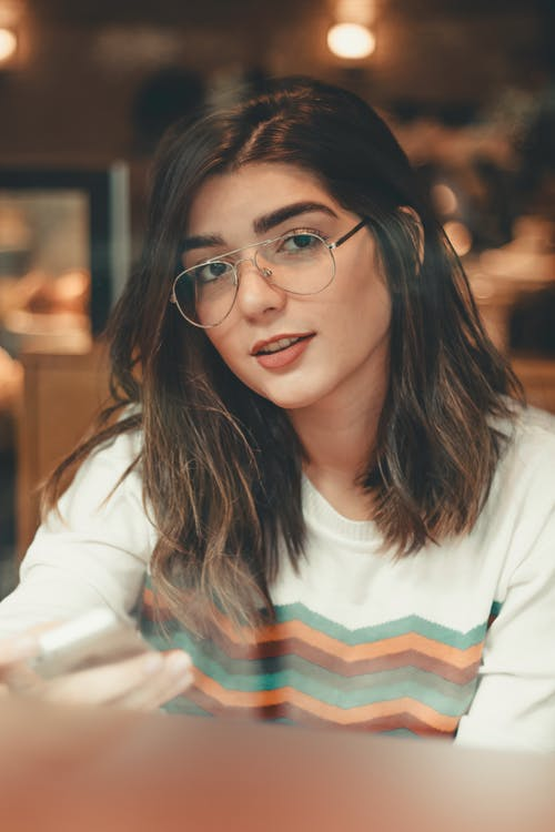 Close-up Photo of Woman in Glasses Sitting at a Coffee Shop