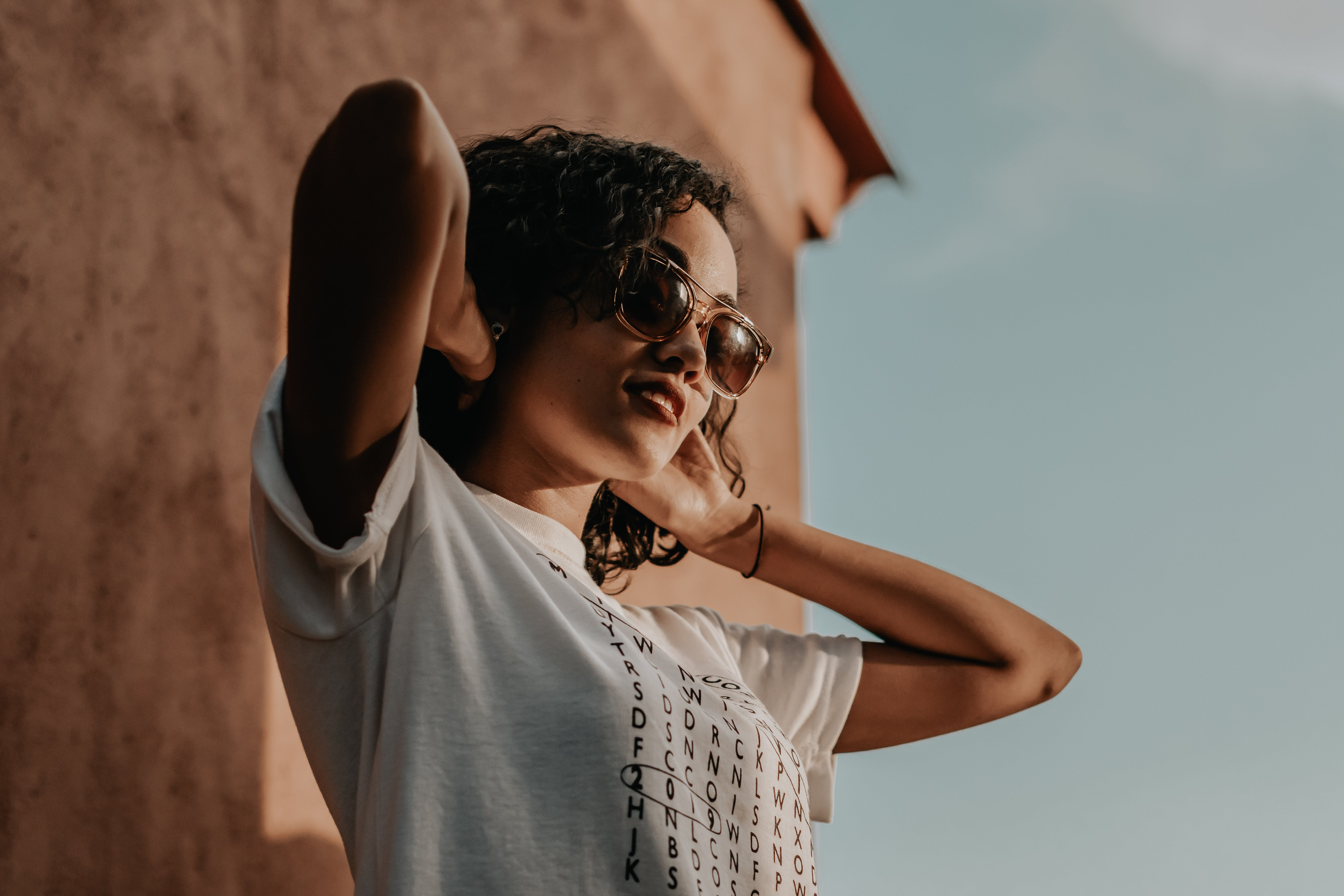 Photo of Woman in Sunglasses and White T-shirt with Her Hands on the Back of Her Head