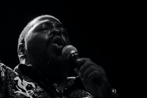 Monochrome Photo of Man Singing