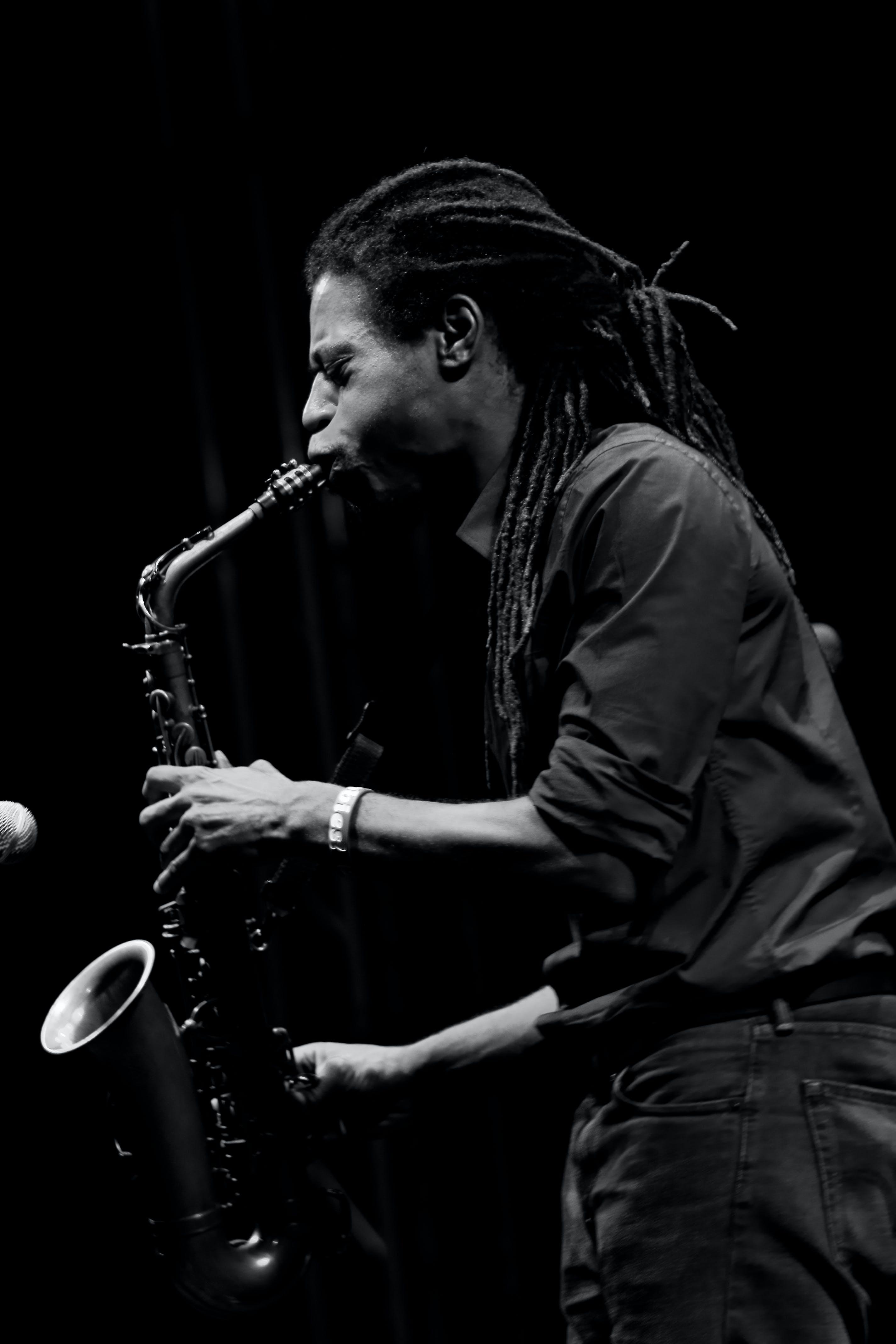 Monochrome Photo of Man Playing Saxophone