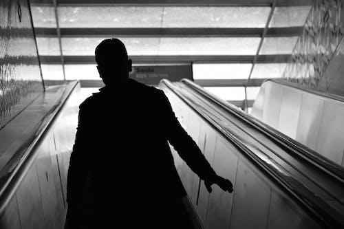 Man Walking on Escalator