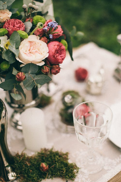 Close-Up Photo of Flowers Near Drinking Glass