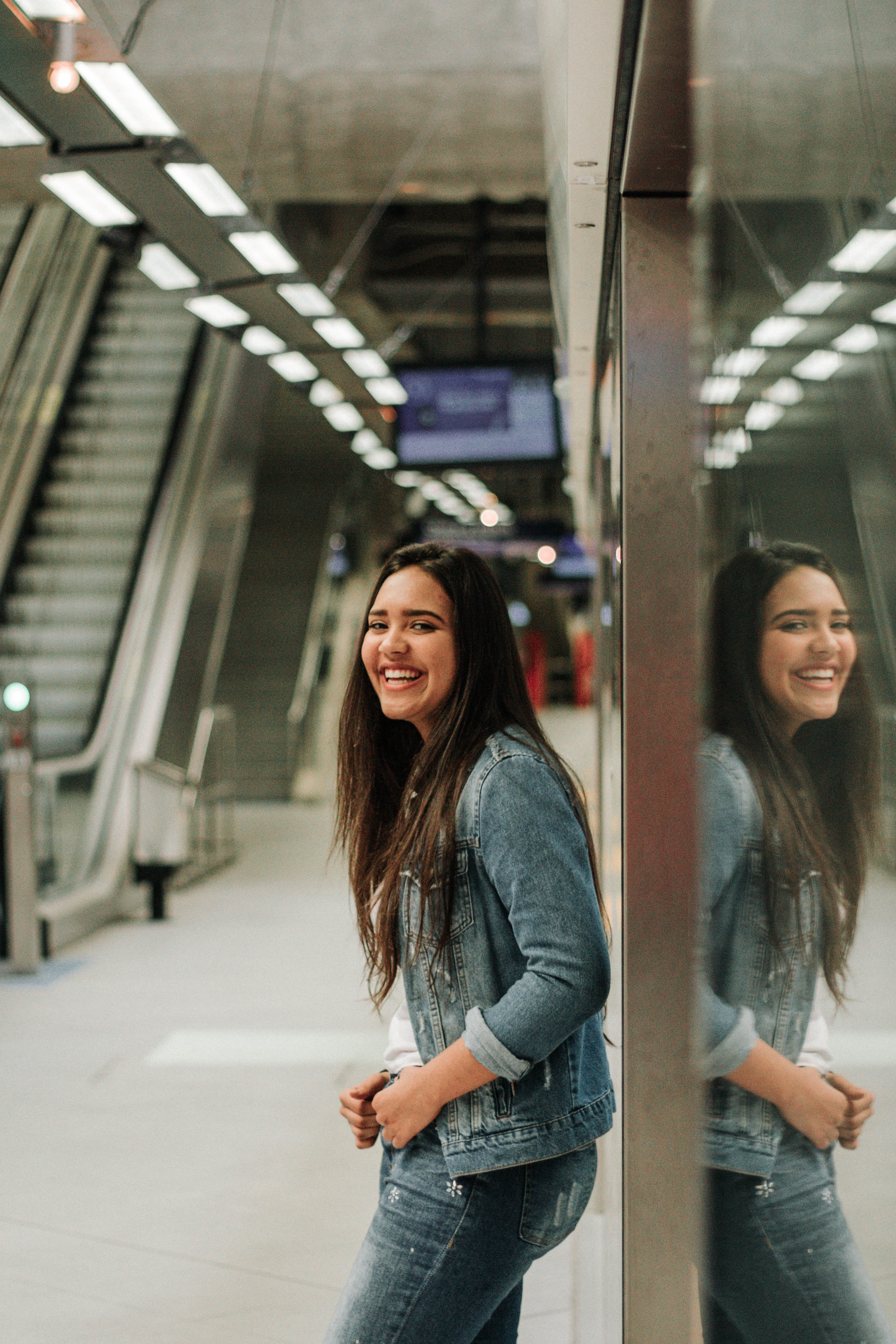 Photo of Laughing Woman Leaning Against Glass Wall