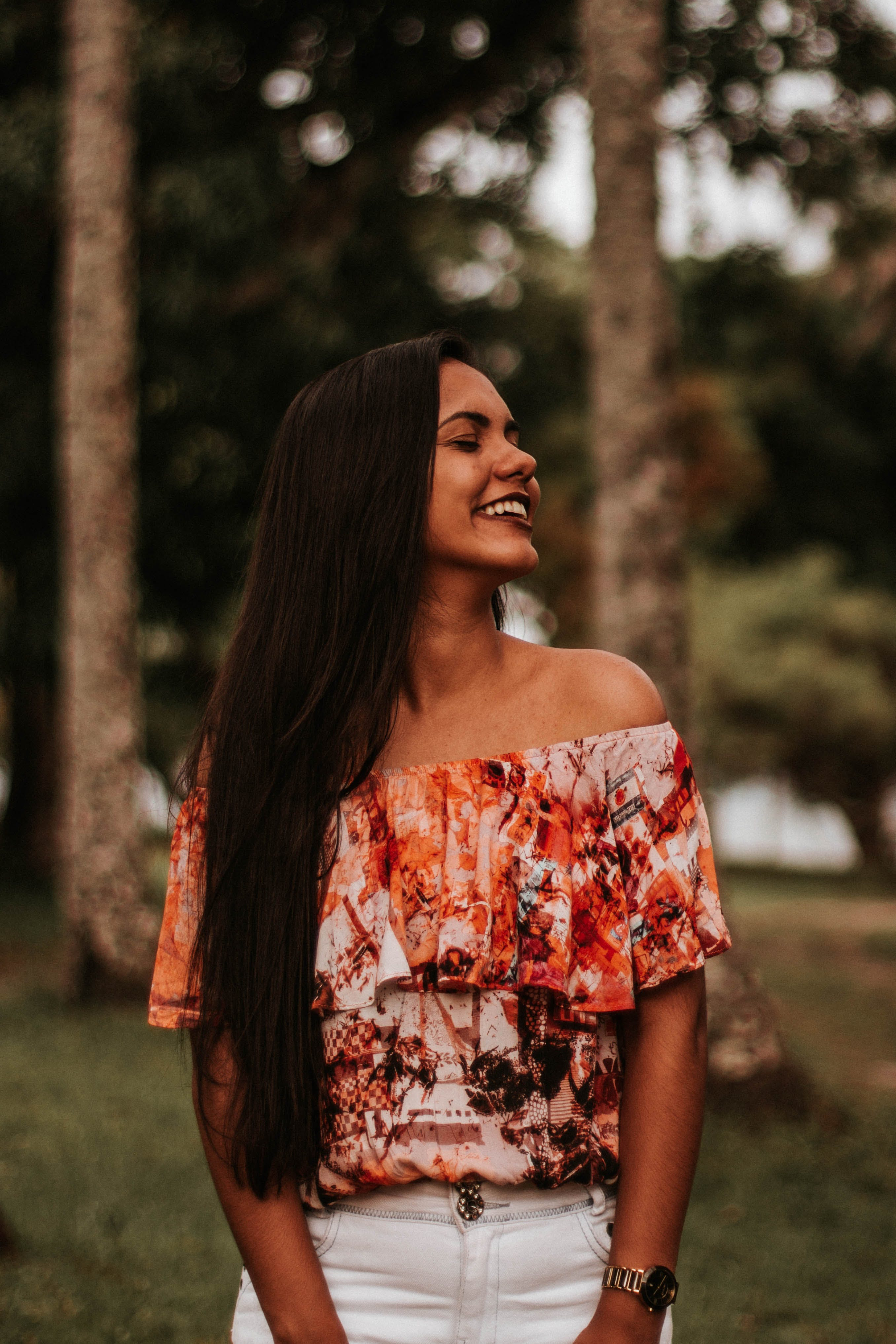 Photo of Smiling Woman in Red and White Floral Top with Her Eyes Closed