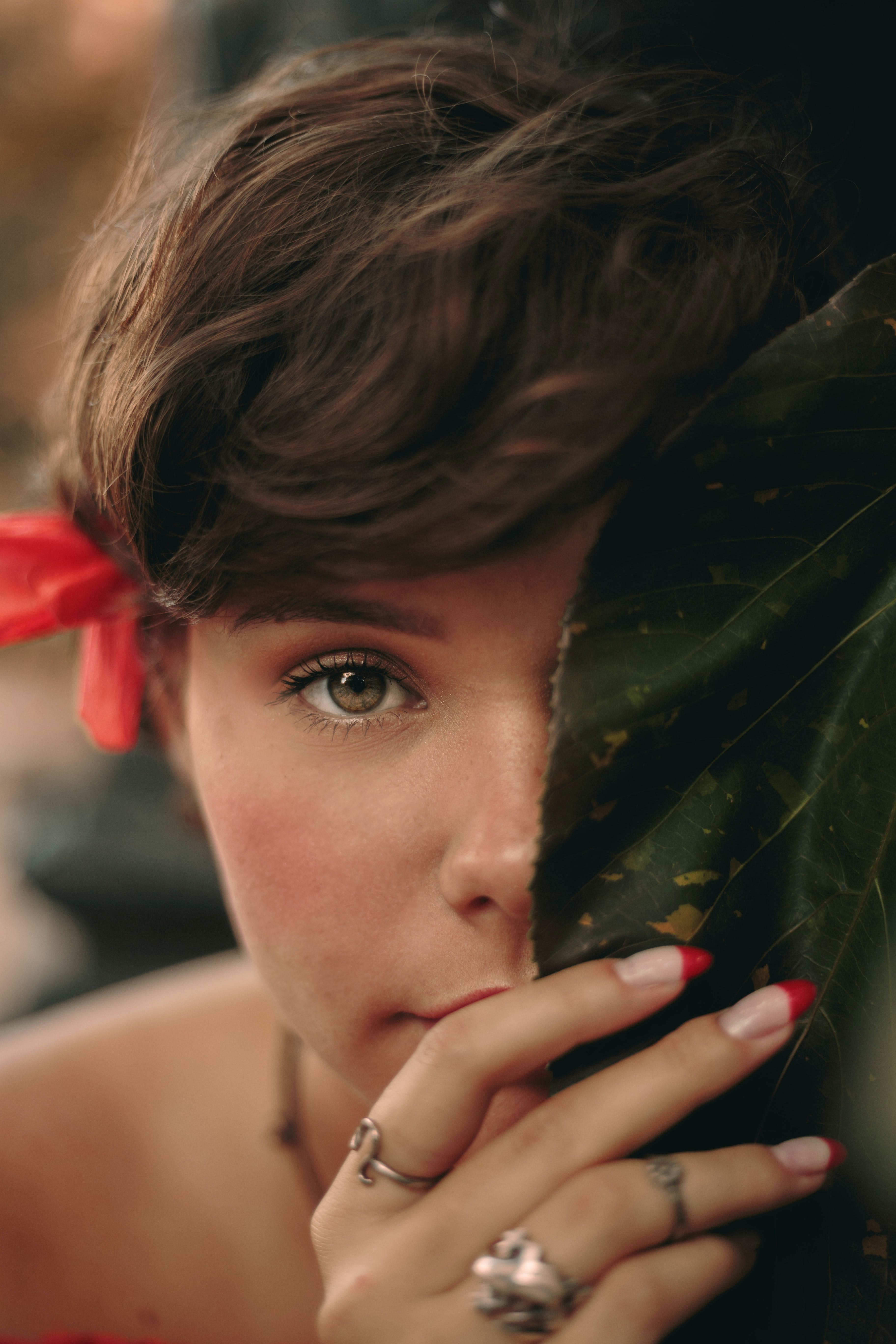 Close-Up Photo of Woman Holding Leaf