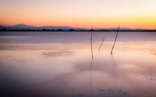 Foto stok gratis long exposure, matahari terbenam, perairan yang tenang
