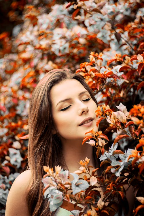 Close-Up Photo of Woman Near Flowers