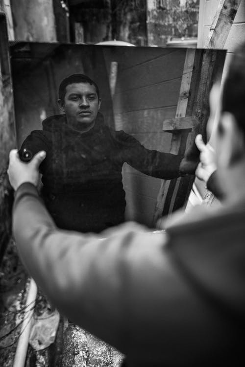 Monochrome Photo of Man Holding a Mirror
