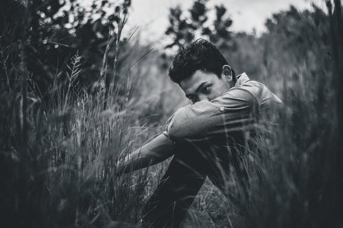 Monochrome Photo Of Man Sitting On Grass