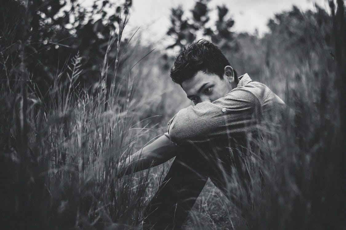 Monochrome Photo Of Man Sitting On Grass