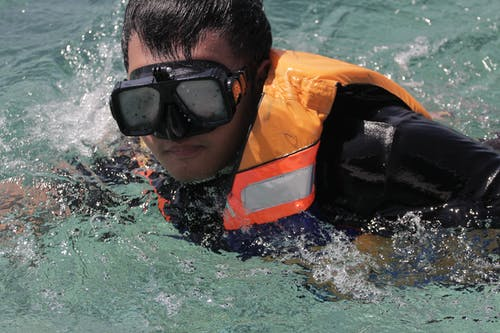 Crop  man in swimming vest and goggles in seawater