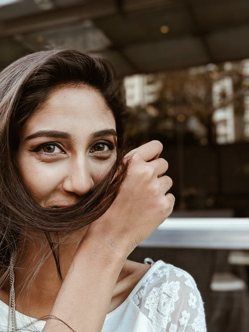 Photo of Woman Holding Her Hair over Her Mouth