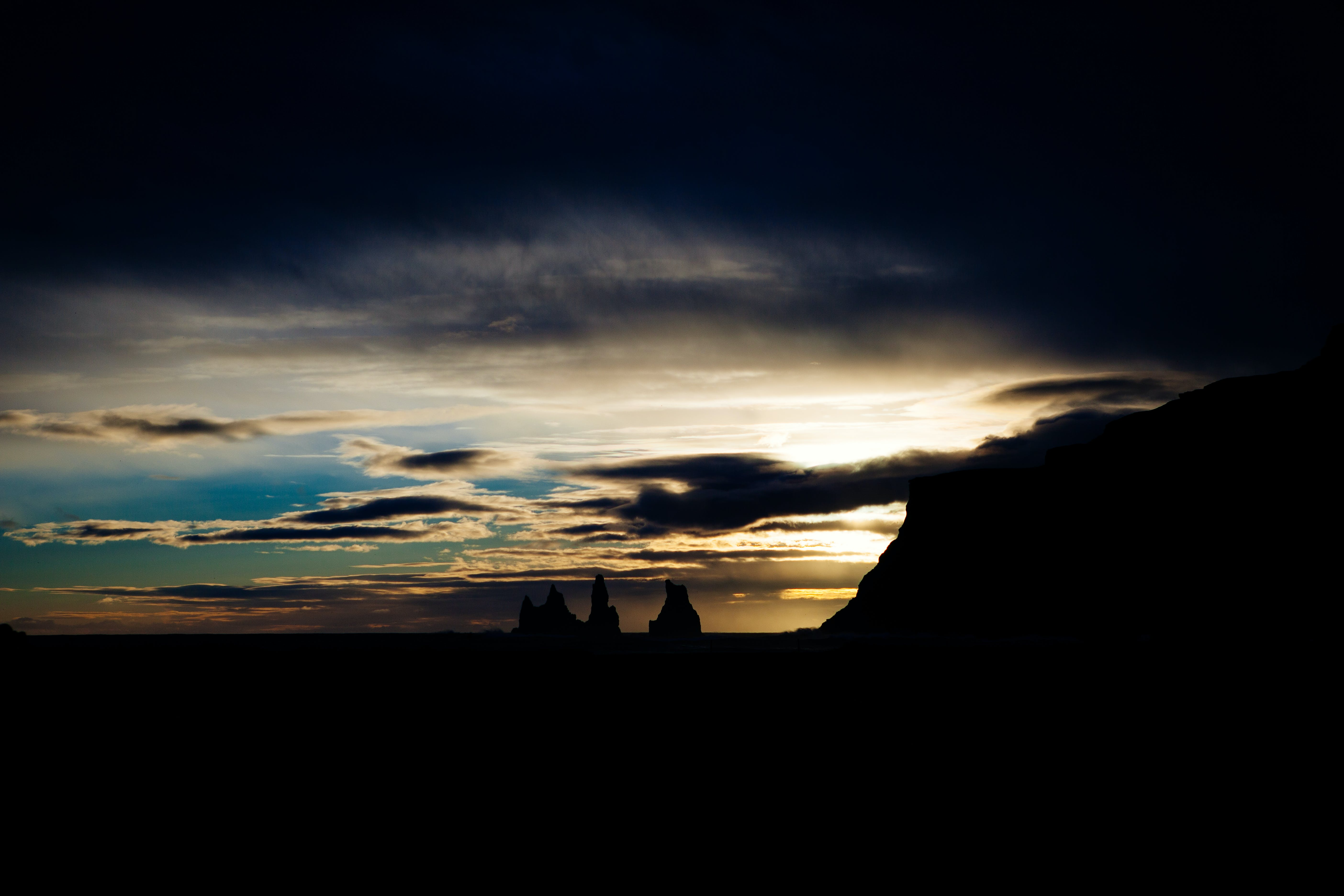 Silhouette of Rock Formations Under Cloudy Sky