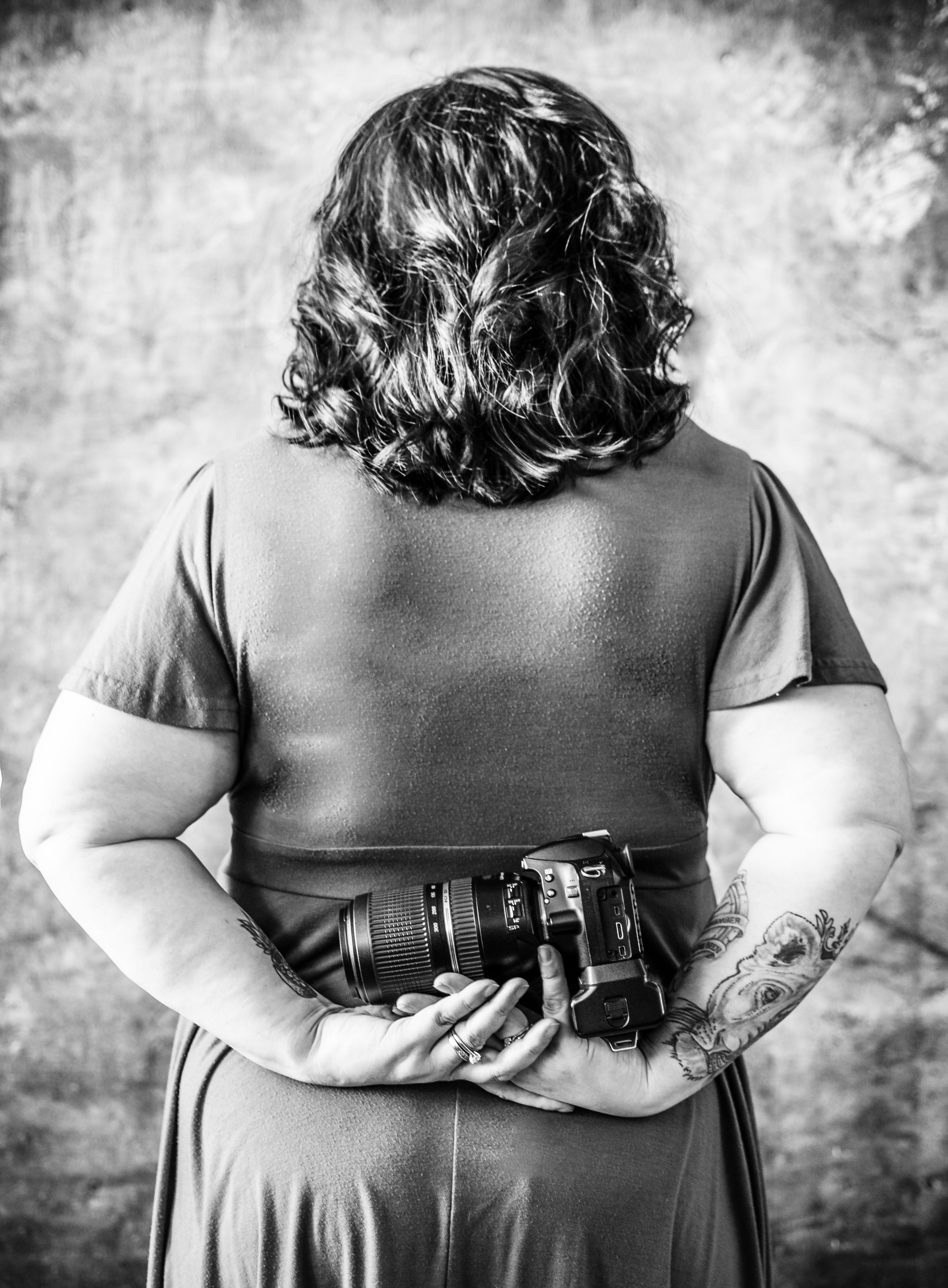 Free stock photo of black and white, from the back, portrait with camera, tattooed photographer