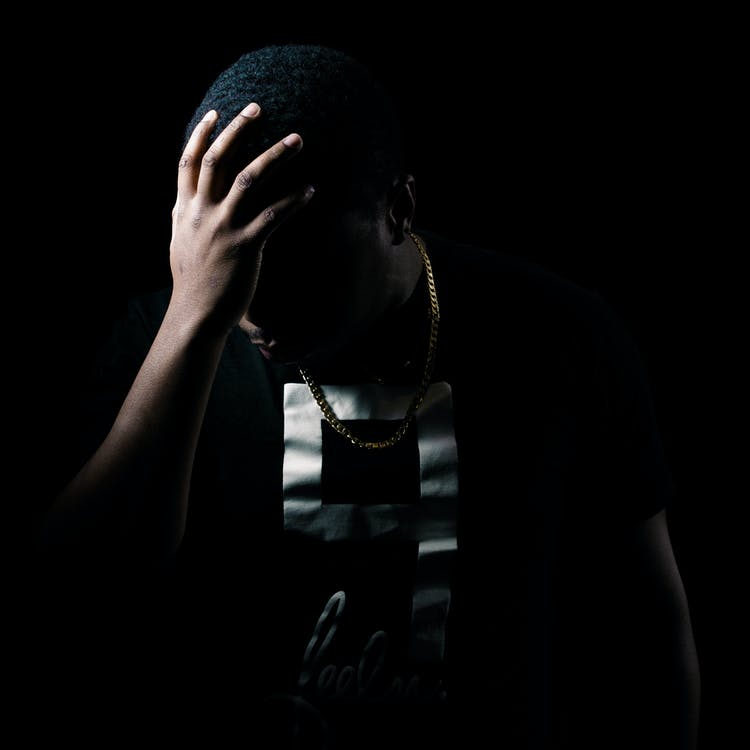 Photo of Man with Hand on His Head in the Dark