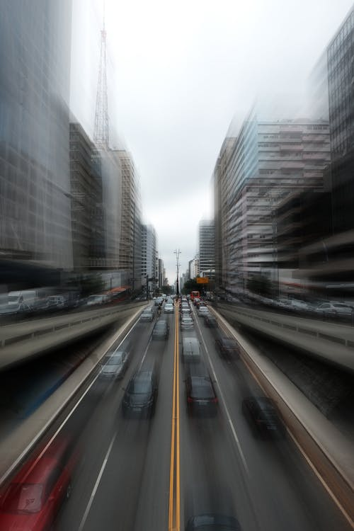 Time Lapse Photography of Cars on Road Between High Rise Buildings