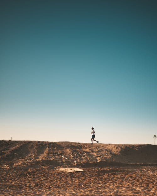 Photo of Person Running on Dirt Road