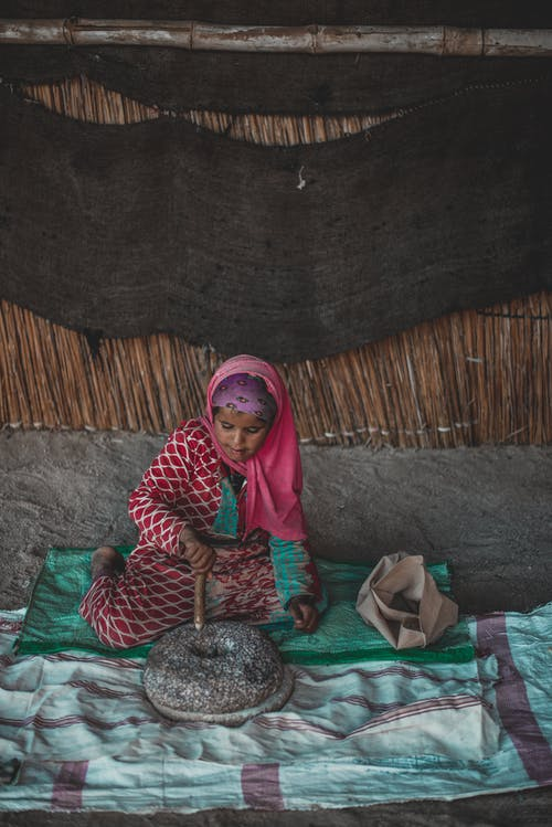 Full body of ethnic woman in traditional clothes sitting on floor with stone utensils in hut