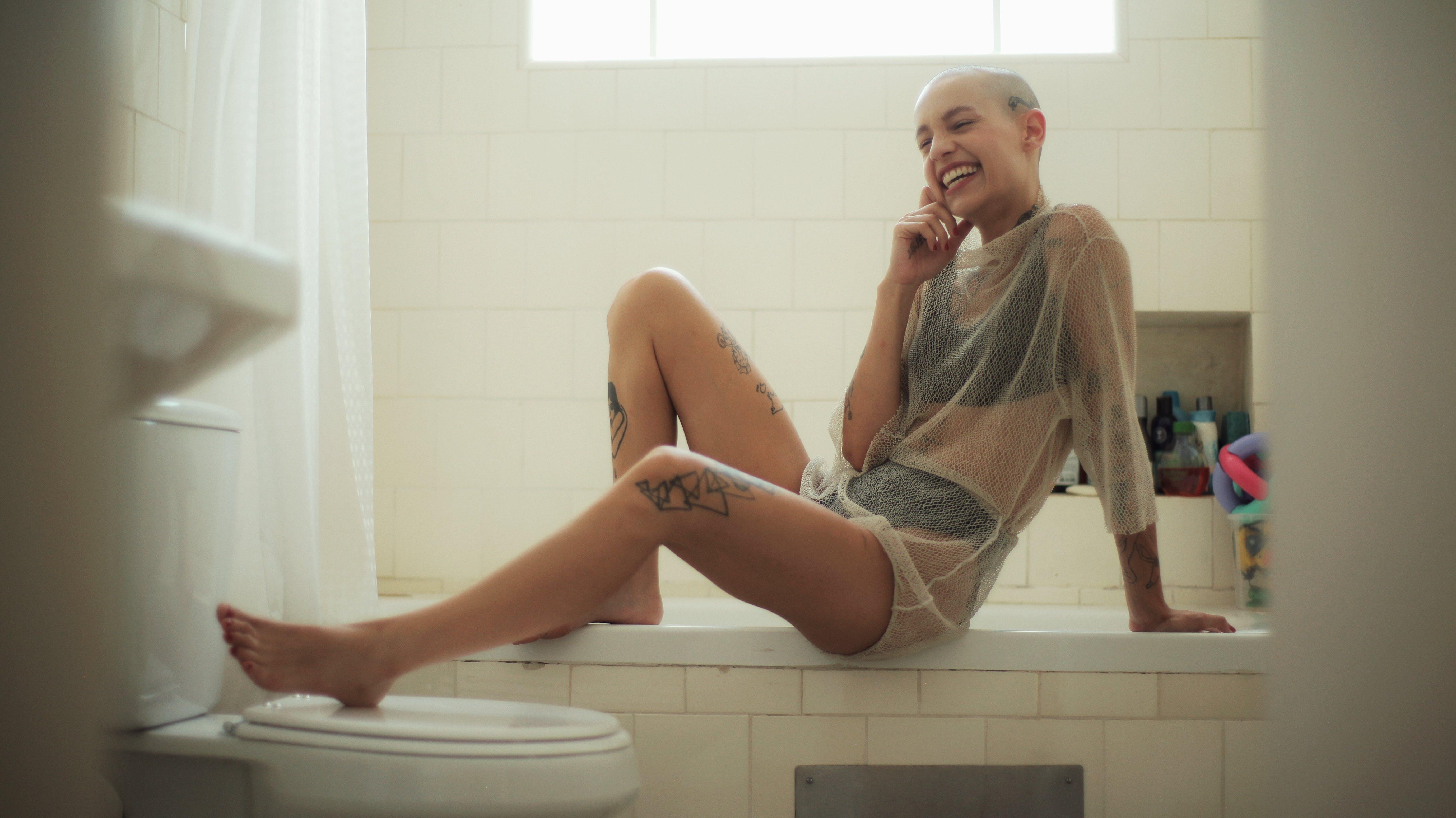 Smiling Woman Sitting On Bath Tub