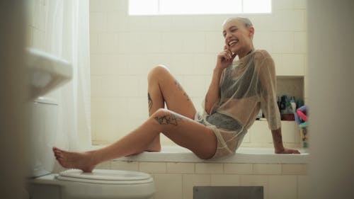 Smiling Woman Sitting On Bath Tub