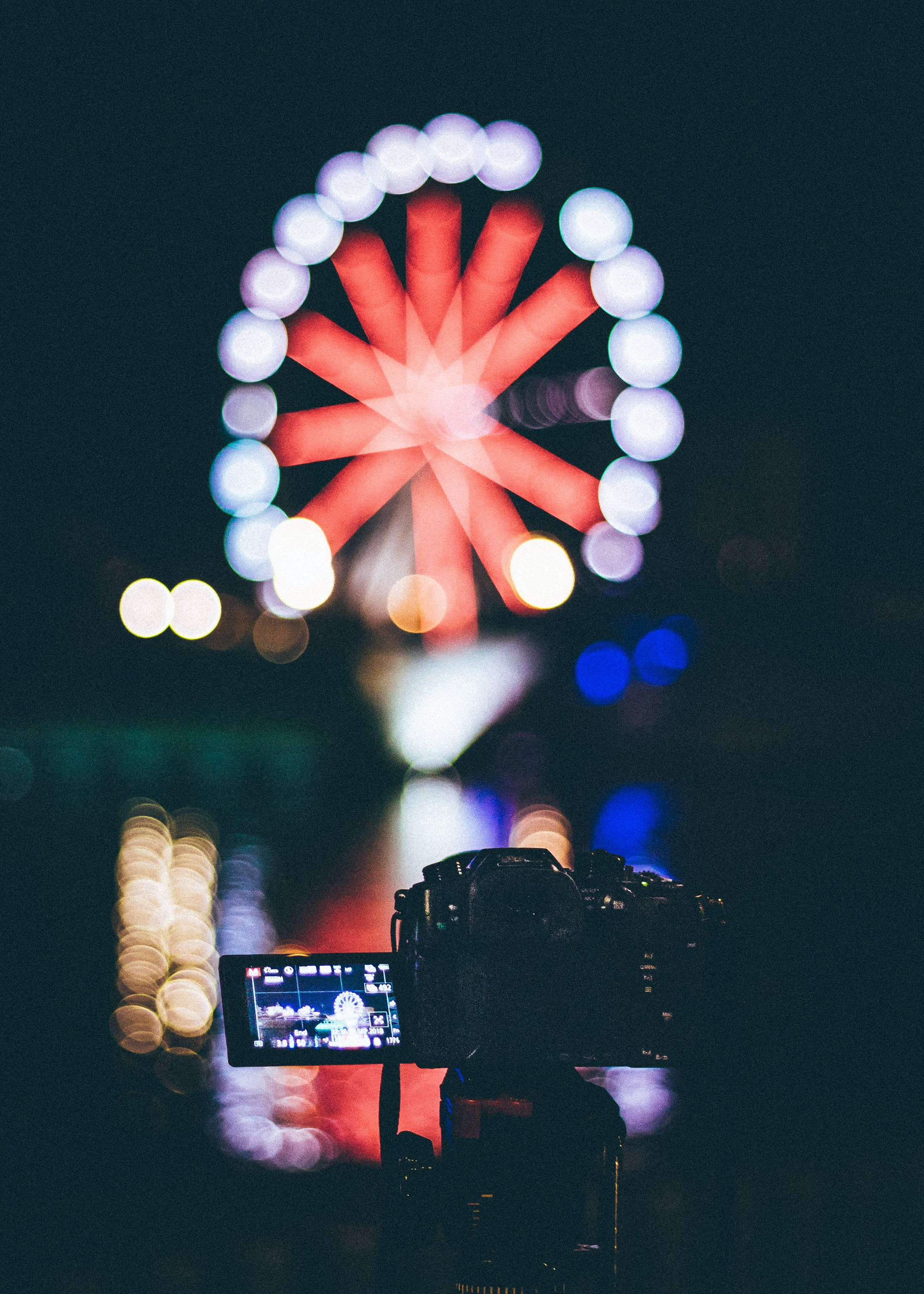 Selective Focus Photography of Dslr Camera With Ferris Wheel Bokeh Lights
