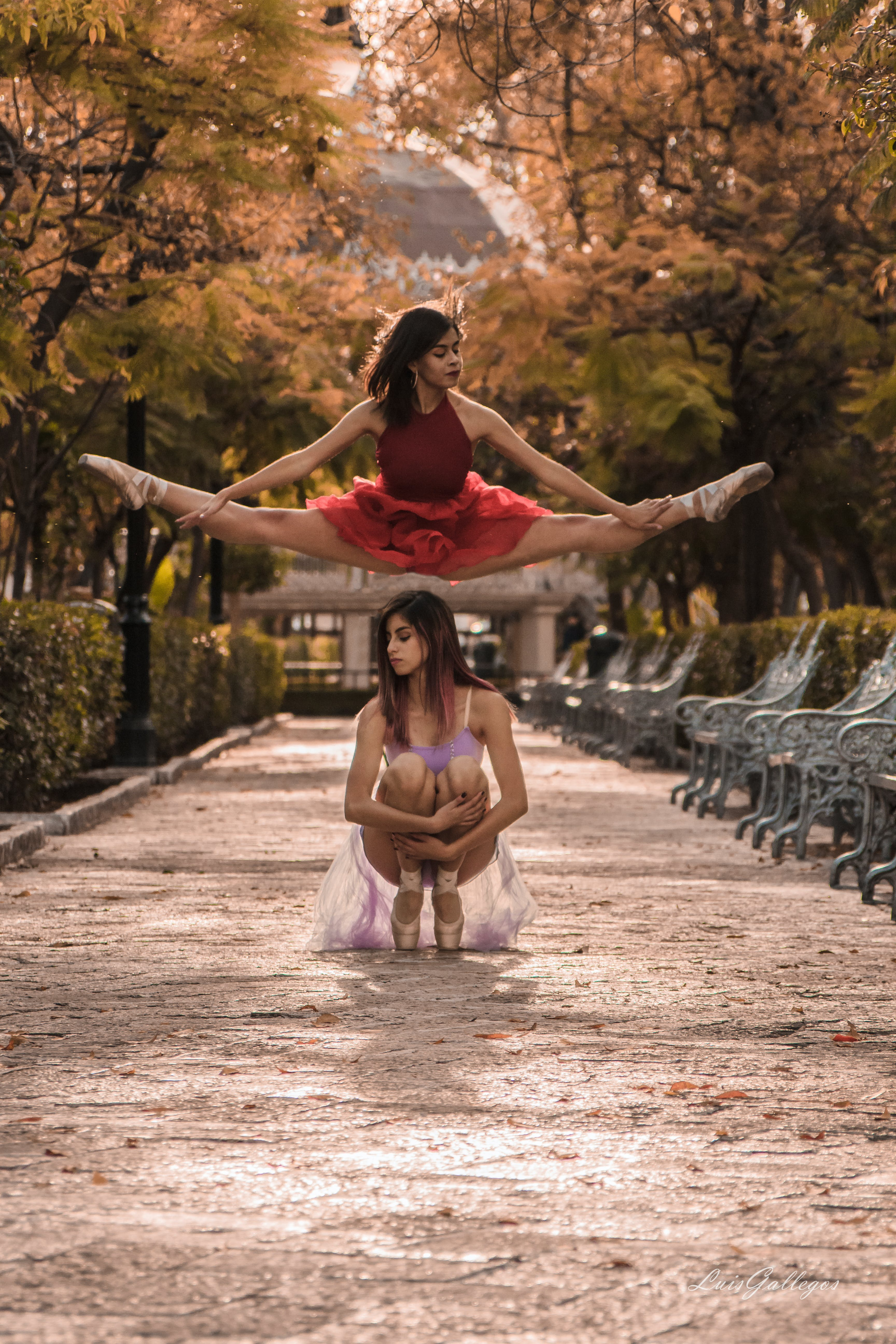 Woman Jumping on Top of another Woman Sitting on Gray Concrete Pathway
