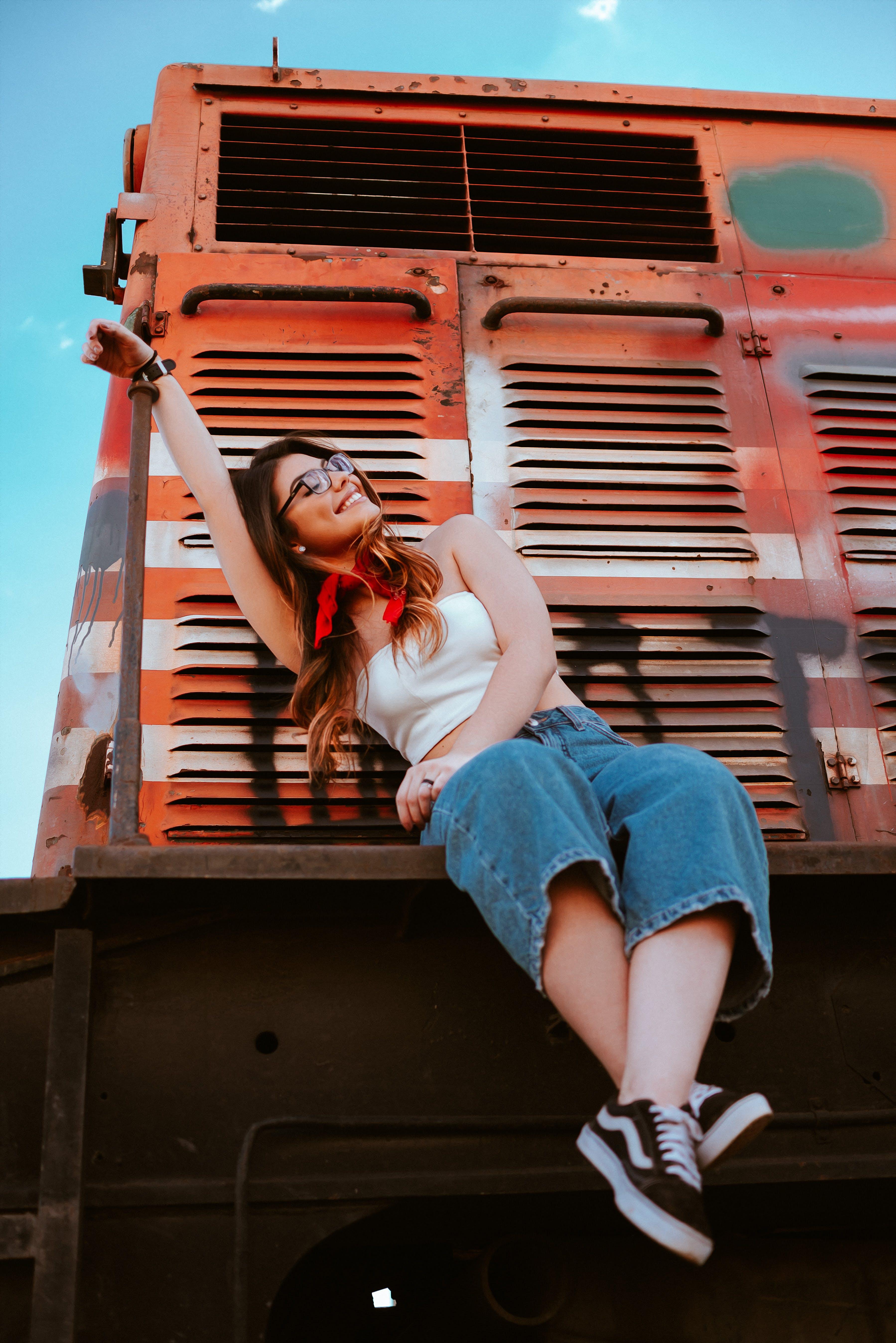 Woman Sitting on Orange and Gray Train Under Blue Sky