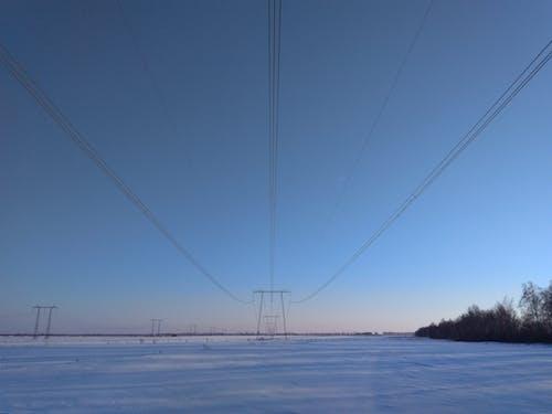 Ilmainen kuvapankkikuva tunnisteilla auringonlasku, kaapelilangat, kenttä, lumi