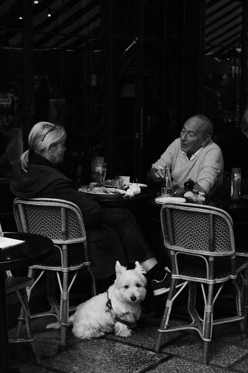 Grayscale Photo of Man and Woman Sitting at a Restaurant